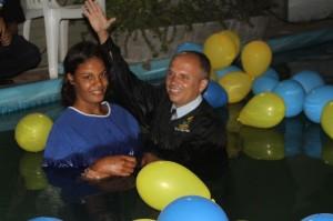 Pastor adventista bautiza a joven conversa, después que ella decidiera entregar su vida a Cristo.  Bautismo por inmersión.