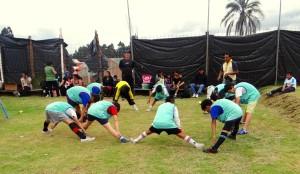 Niños realizando calentamiento para entrar en el campo de juego de fútbol indoor.