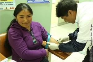 Mary sonríe ante la extracción de su sangre.  Crédito de foto: Freedom from Hunger.
