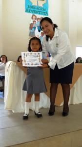 Docente del centro educativo reconoce el esfuerzo de una de las estudiantes.