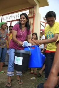 Mujer carga donativos distribuídos, por ADRA, en una ciudad de filipinas.