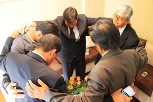 Pastores reunidos en un grupo pequeño oran por la programación a desarrollarse en Semana Santa.