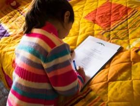 Niña beneficiada firma la entrega de su primera cama nueva, en Chile.