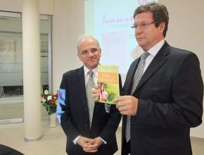 El Dr. Hugo Cettour con el libro Viva con Esperanza, junto al Dr. Kenny Vicente.