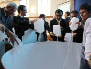 Pastores llenan tanque de agua para demostrar la integración en la misión.