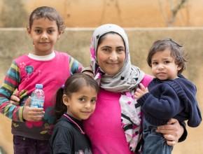 Madre siria, refugiada en el Líbano, junto a sus tres pequeños hijos. ADRA acoge a esta familia.
