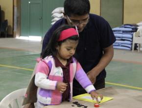 Atividades de manualidades sendo realizados con uno de los niños