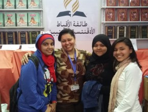 Booth co-manager Ranya Maher, second left, posing with visitors. [photo: Amgad Nageh]