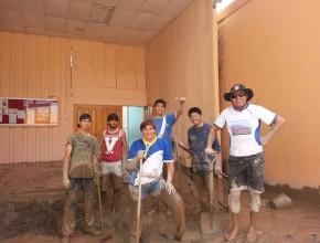 Líderes de Conquistadores en acción. Jóvenes sacan el barro que entró a la escuela adventista de Copiapó.