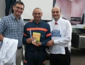 Luciano al centro y en sus manos el libro Viva con Esperanza. A los costados médicos adventistas que ofrecen sus servicios en la Unidad Móvil de Salud.